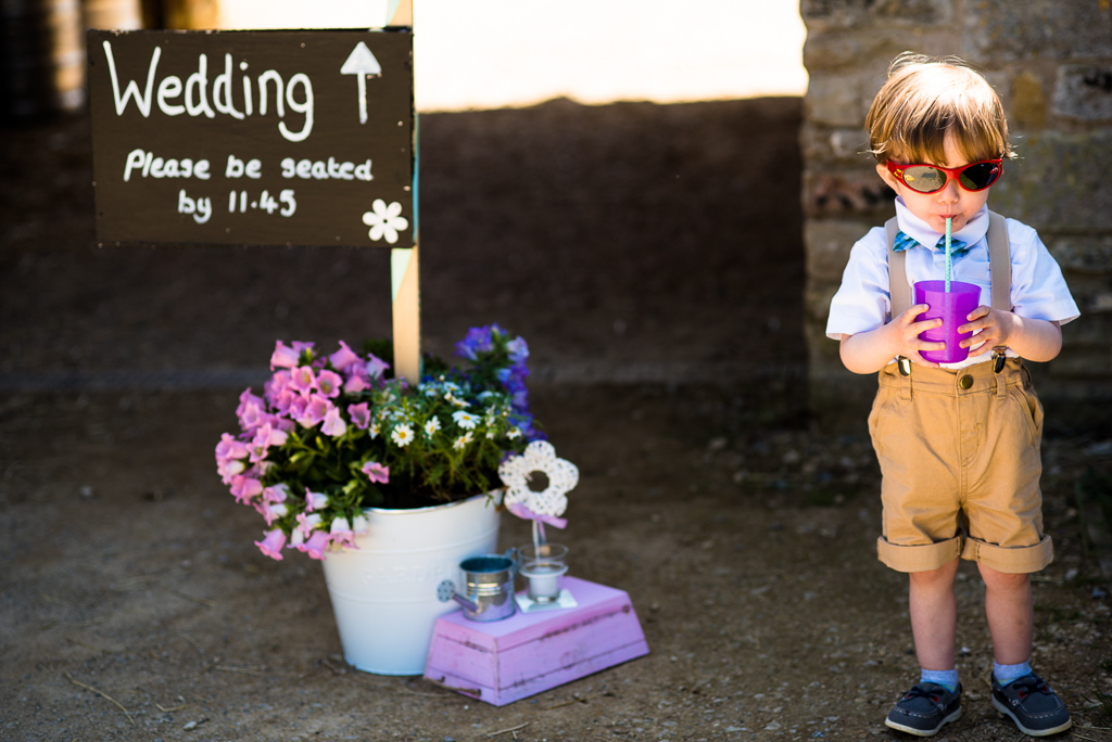 A child drinking from a beaker at a wedding.