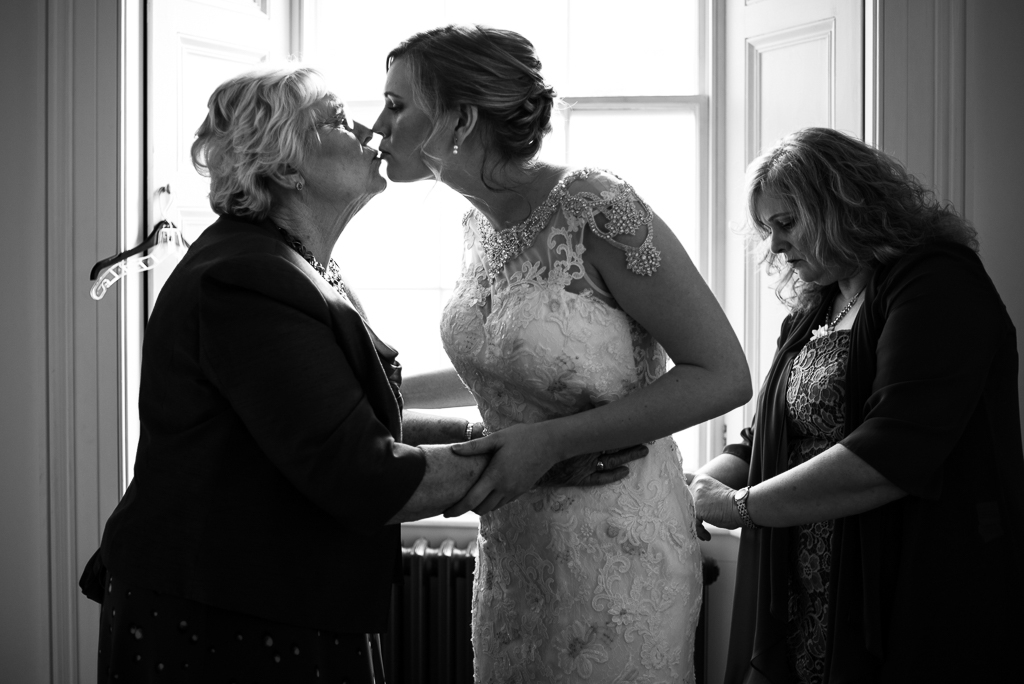 A bride kisses her grandmother as she gets ready for her wedding.