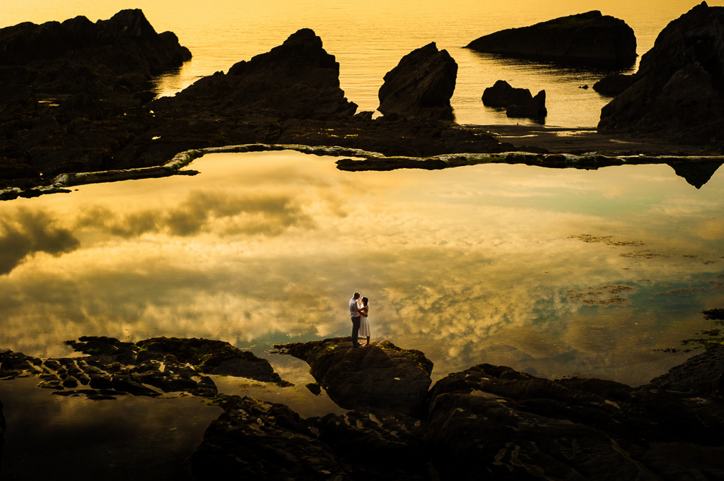 A bride and groom at Tunnels Beaches during sunset.