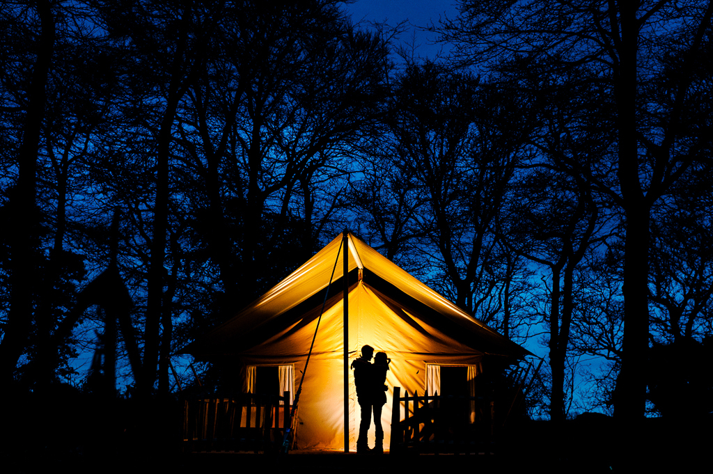 A couple in silhouette against a warmly lit tent and a blue sky.