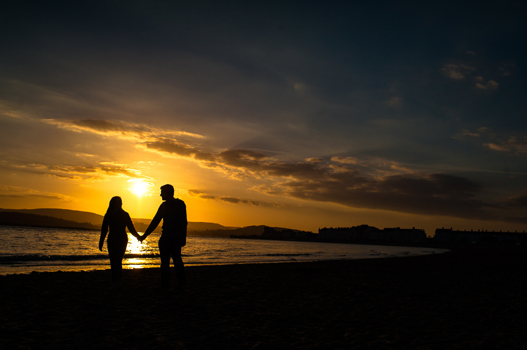 A couple walk hand in hand on the beach at sunset.
