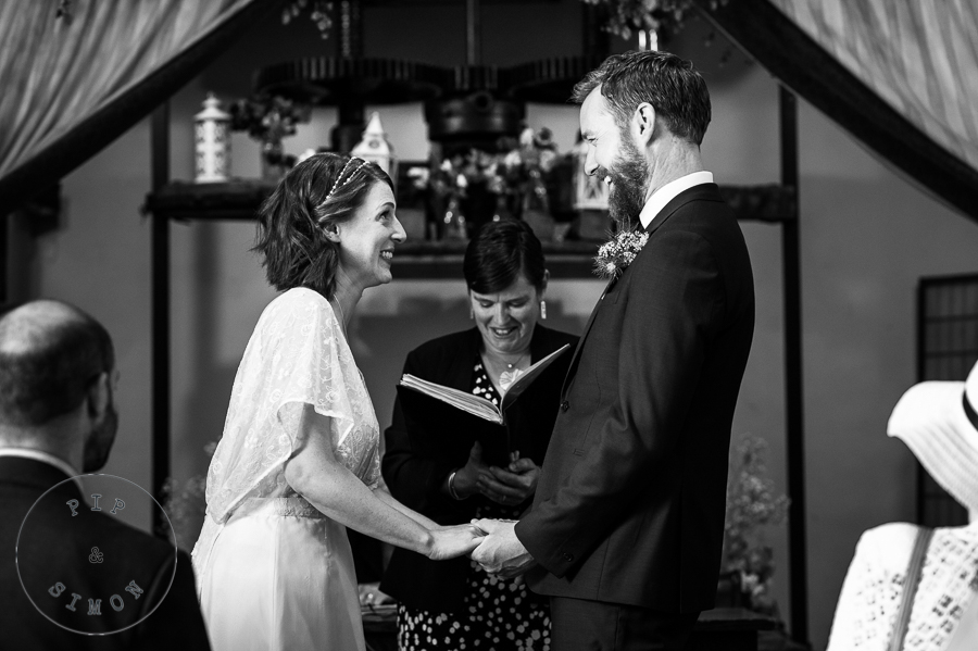 A bride and groom laugh during their wedding ceremony.