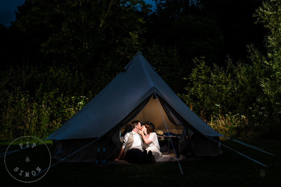 A wedding couple relax in a tent at their festival wedding.