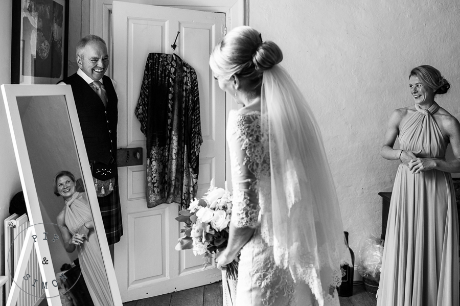 A father sees his daughter in her dress for the first time.