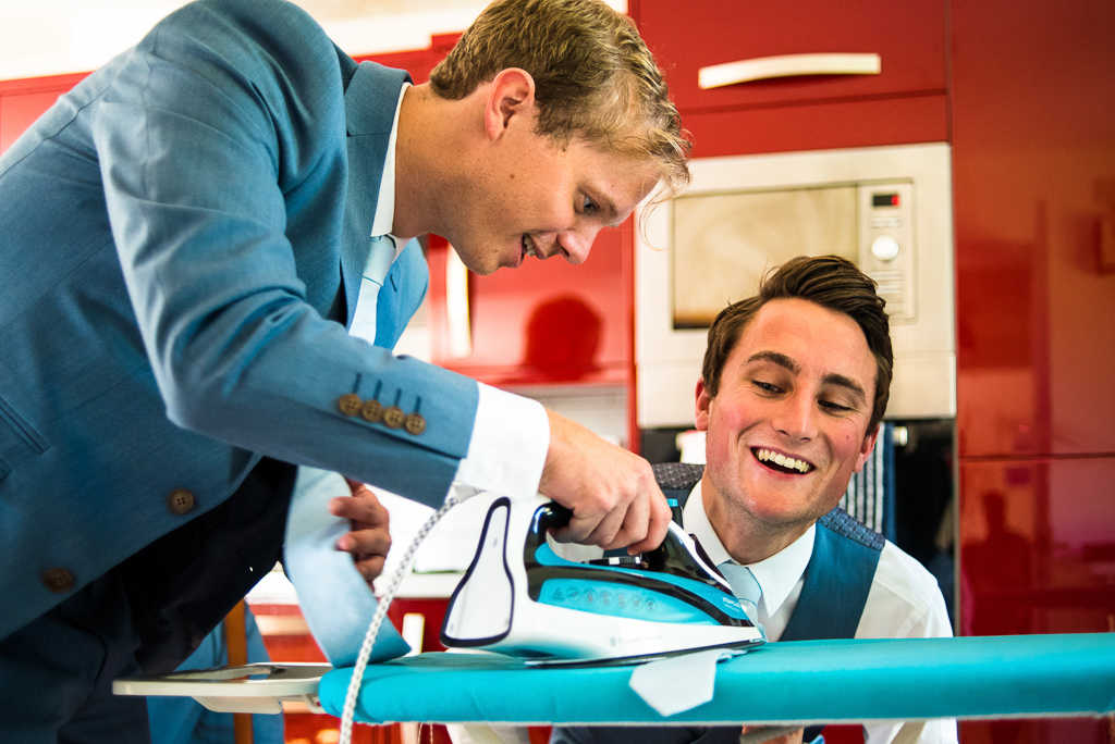 A comedy photo of a man ironing his friends tie while he wears it.
