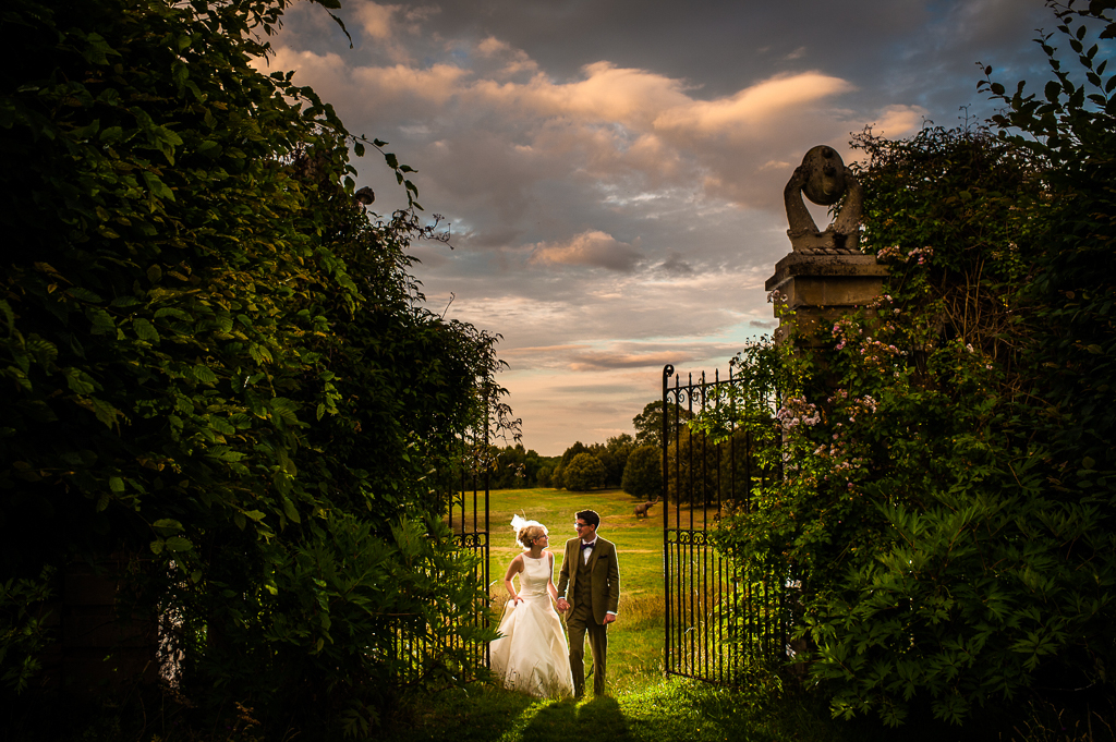 A couple walk together through some ornate gates at a country estate.