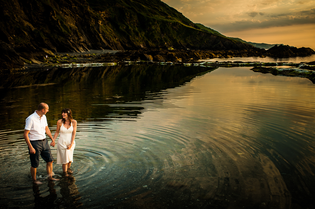 A couple walk in a tidal pool at sunset.