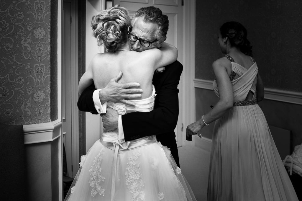 An emotional father hugs his daughter before her wedding.