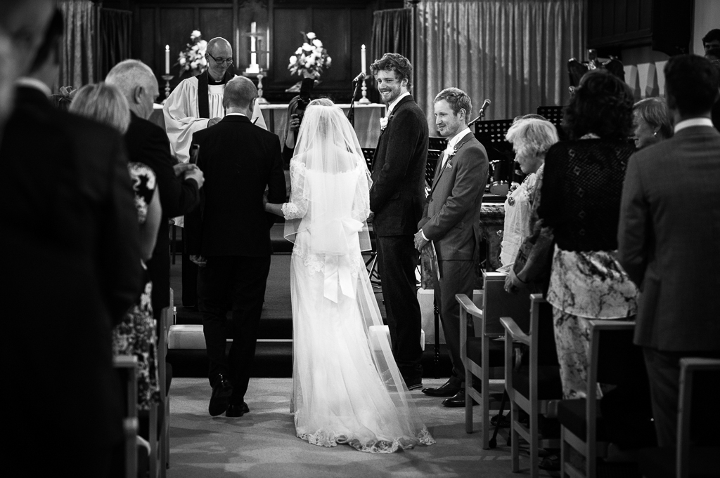 A groom smiles at his bride as she walks down the aisle.