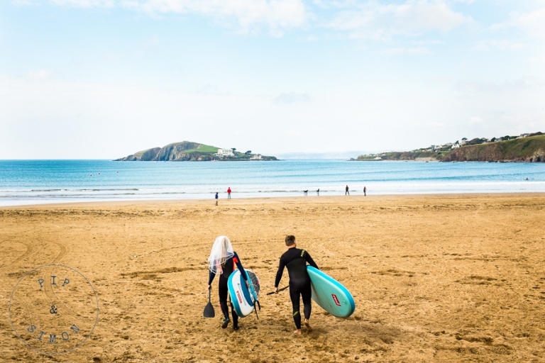 A bride in a veil and a groom head across the beach for a surf before their wedding ceremony.