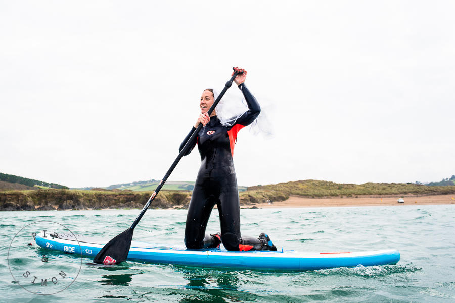 A bride wearing a veil on a paddleboard before her wedding.