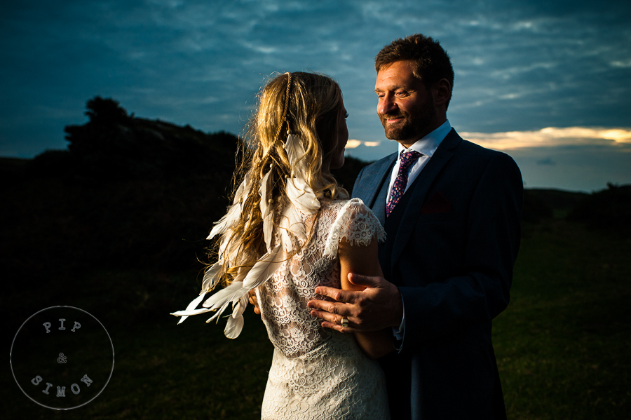 A groom looks at his bride at dusk