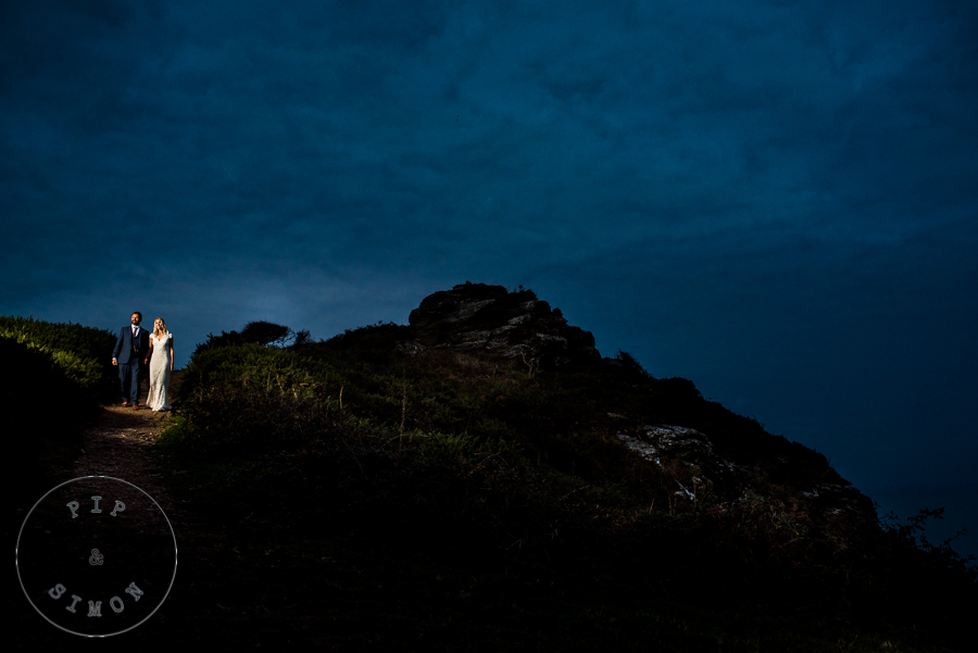 A bride and groom walk on the Salcombe coast path in the evening.