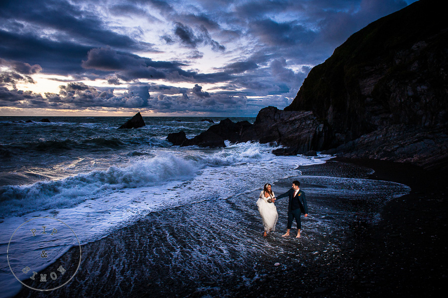 A couple walk on the beach with a dramatic sunset.