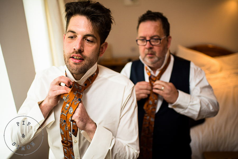 A groom dresses before his wedding.
