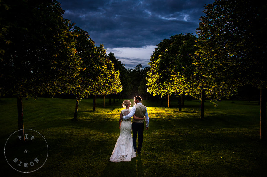 A bride and groom walk through trees at dusk