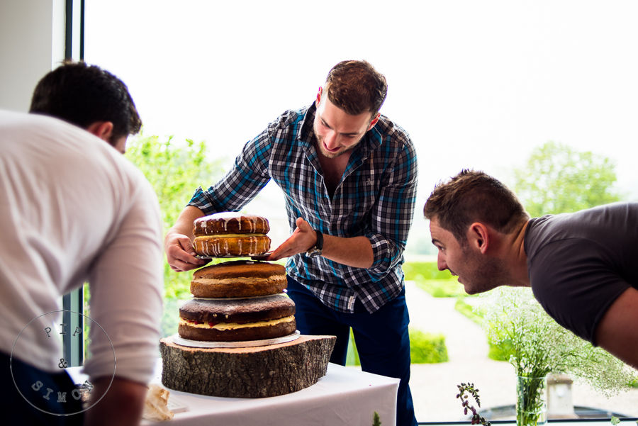 A cake is being assembled prior to a wedding reception
