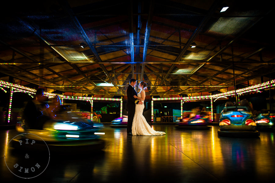 A couple stand as dodgems drive around them at a wedding.