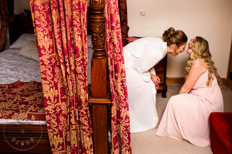 A bride and bridesmaid laugh while getting ready for the wedding.