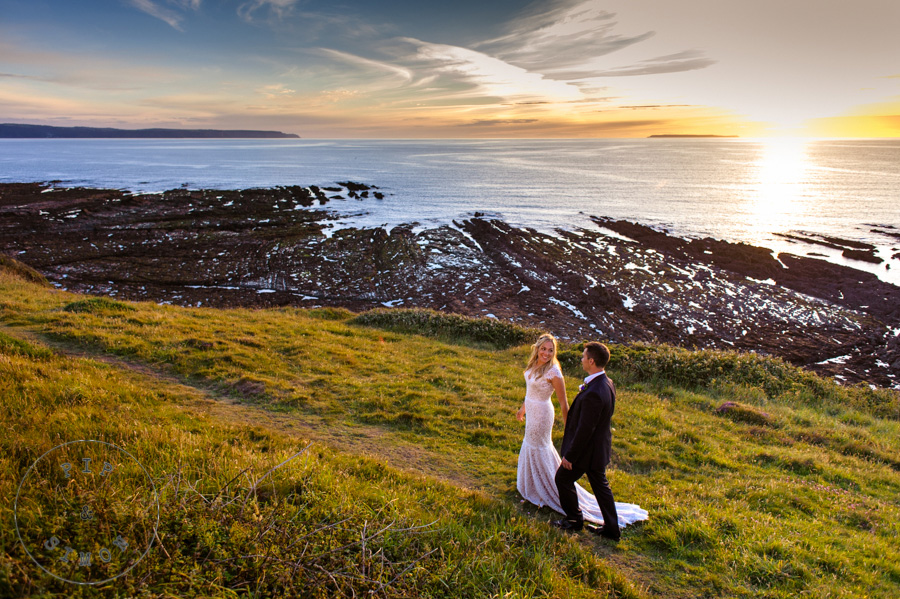 A bride and groom walk on the cliffs in North Devon.