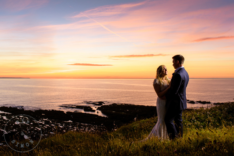 A bride and groom stand on the coastal path at sunset