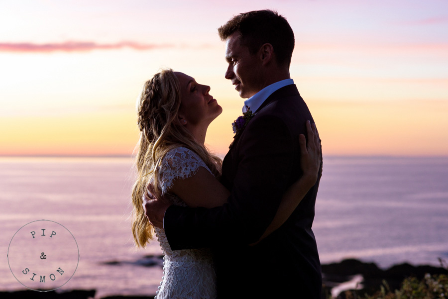 A bride and groom embrace against a pink sky