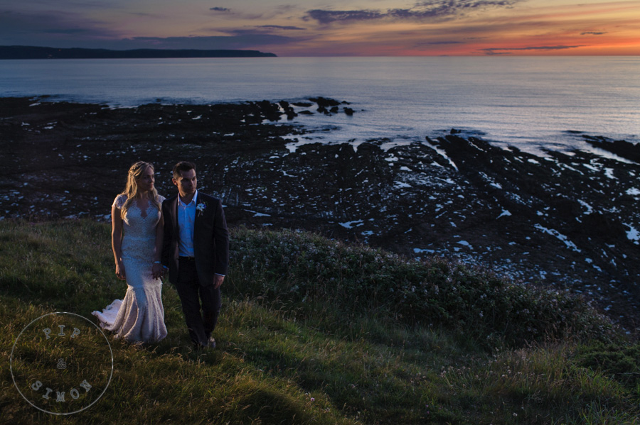 A wedding couple on the coastal path at dusk.