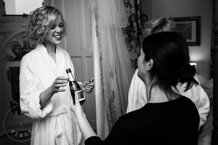 A bride laughs with bridesmaids while preparing for her wedding.