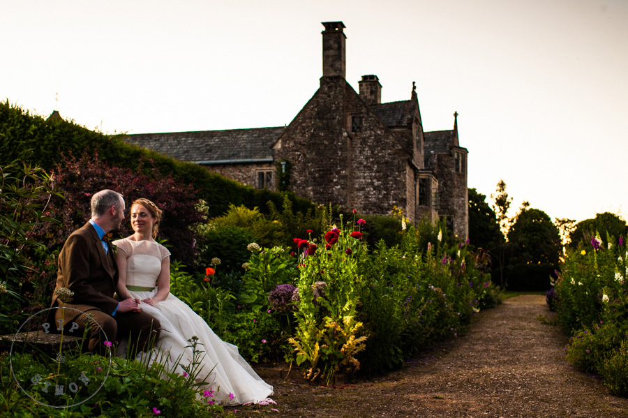 A bride and groom talk in gardens at Cadhay, Devon.