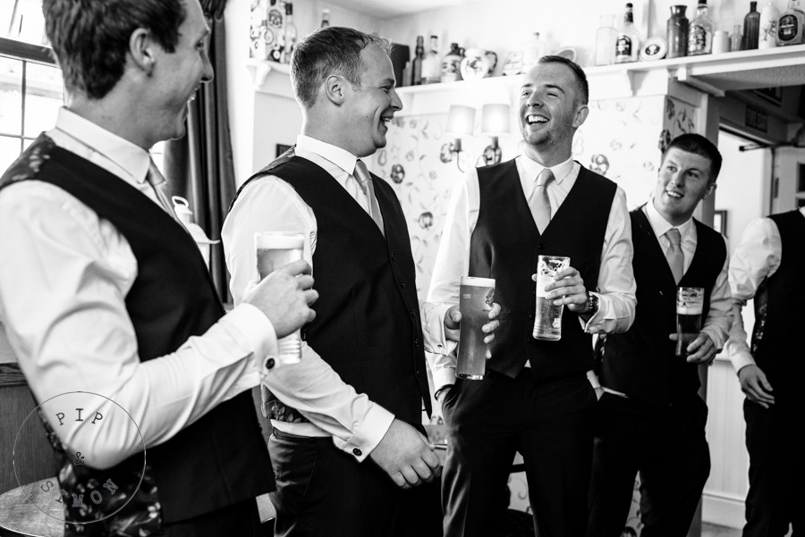 Groomsmen laugh together in a pub.
