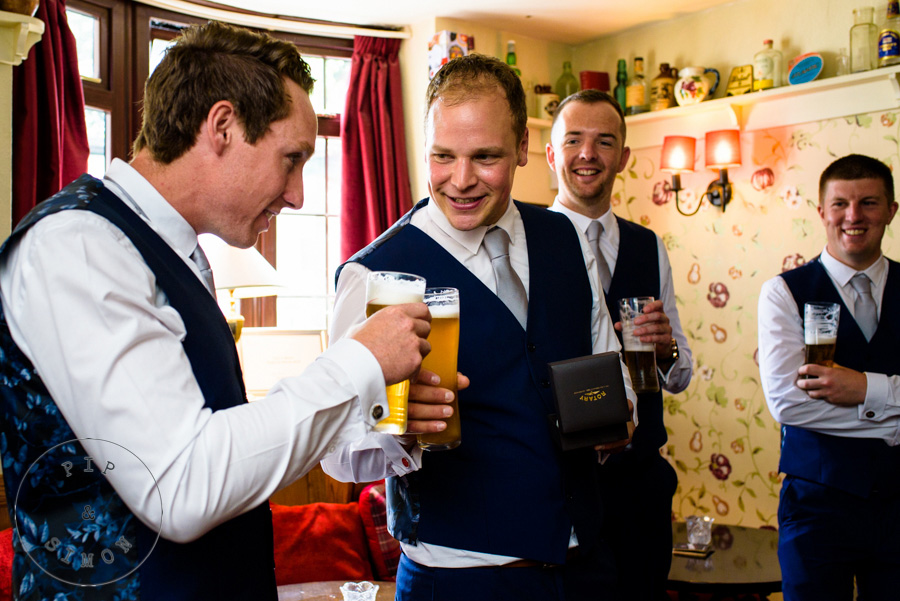 Groomsmen toast together in a pub.