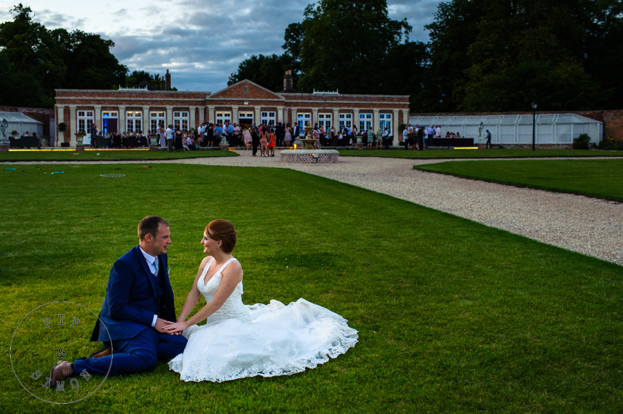 A bride and groom sit together with their wedding venue and guests in the background.