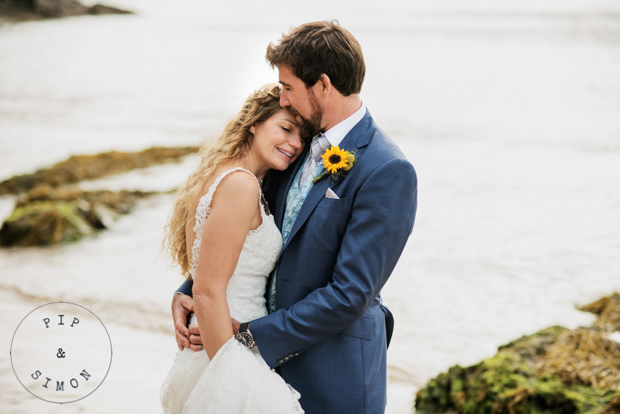 A bride and groom embrace on the beach in Salcombe