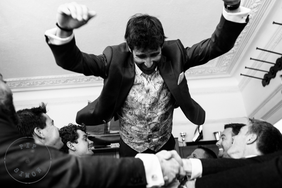 A groom jumps into the arms of groomsmen.