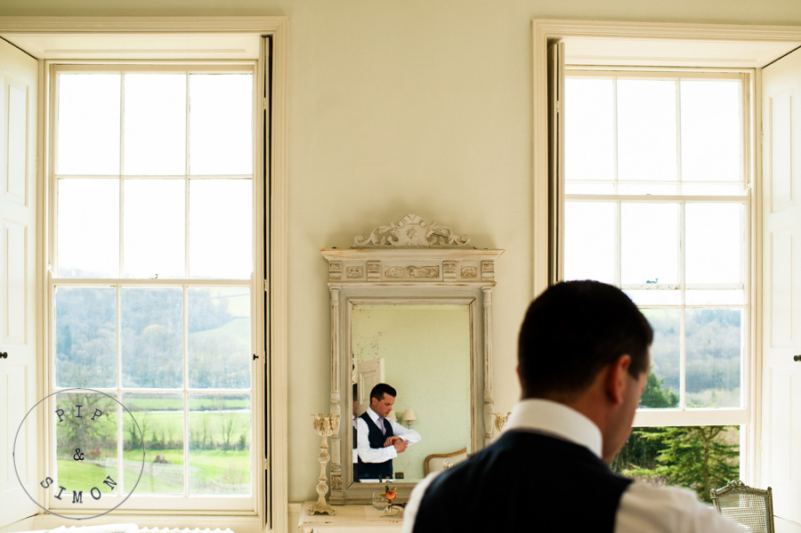 A reflection of a groom preparing for his wedding
