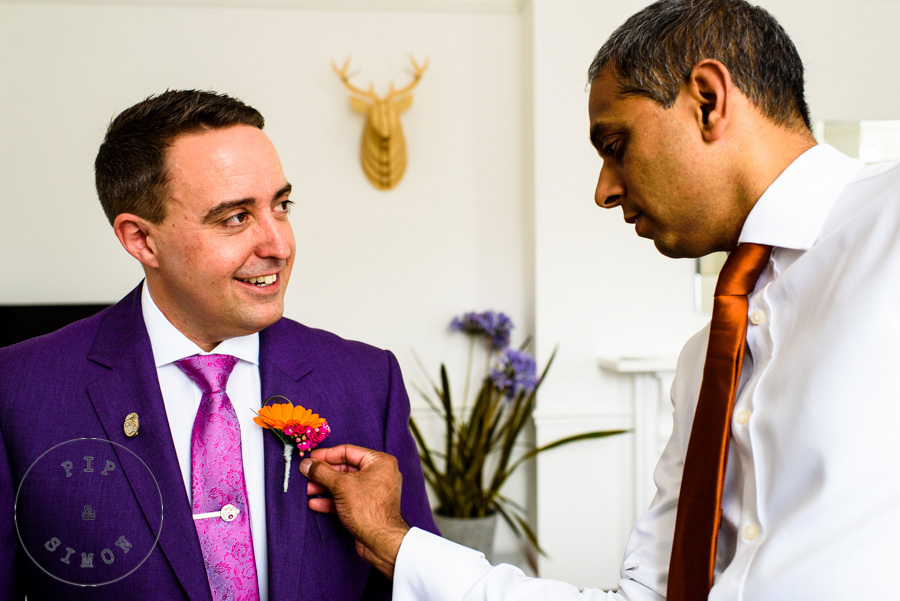 A groom and a groomsman prepare for a wedding
