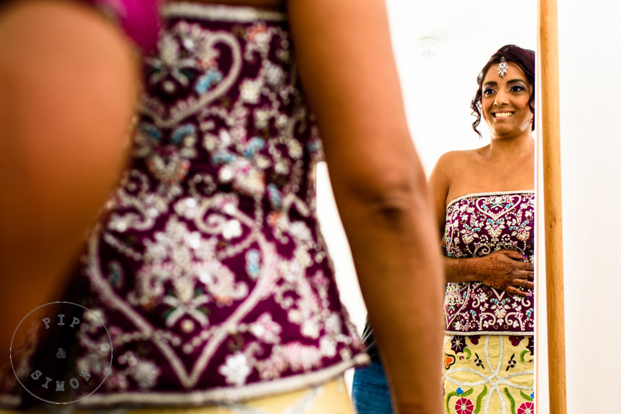A bride looks in a mirror while preparing for her wedding.