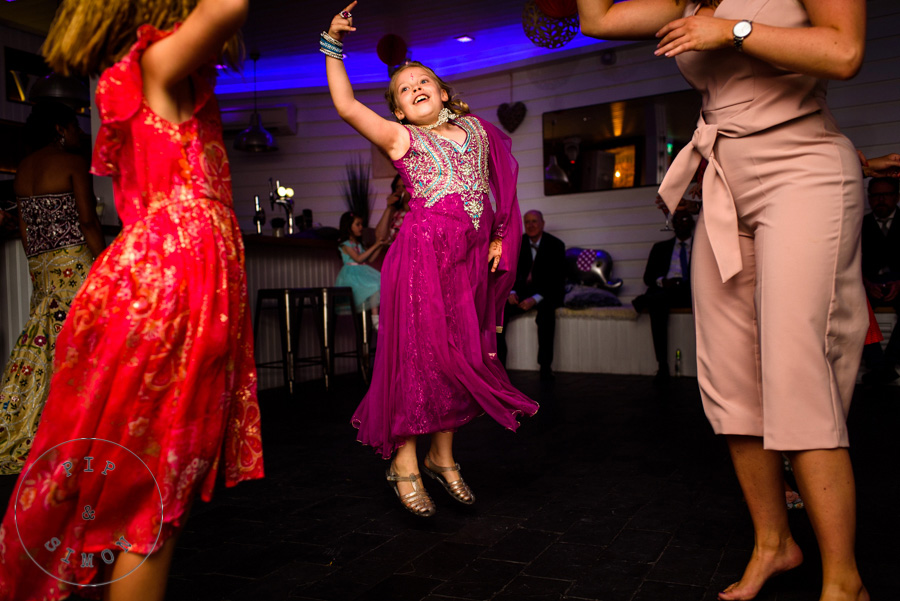 Children jump in the air while dancing at a wedding