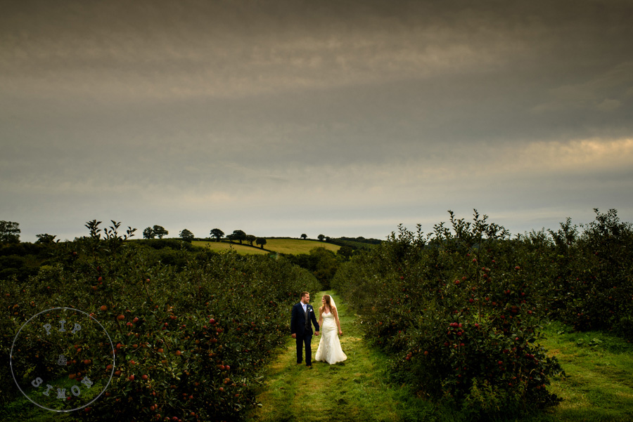 A bride and groom walk in an orchard at dusk.