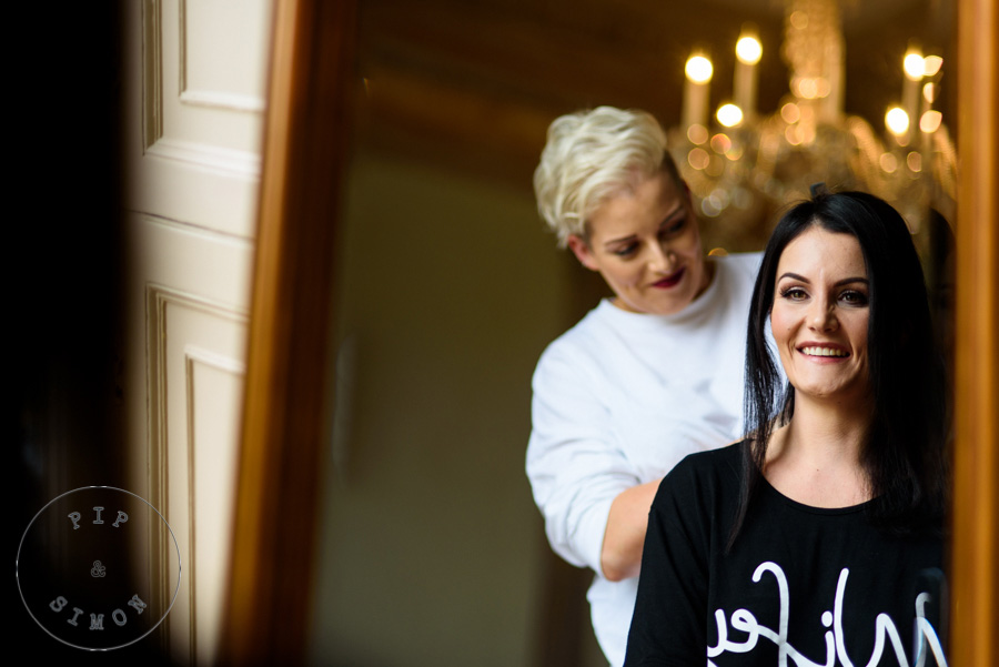 A bride and a hair stylist before the wedding.