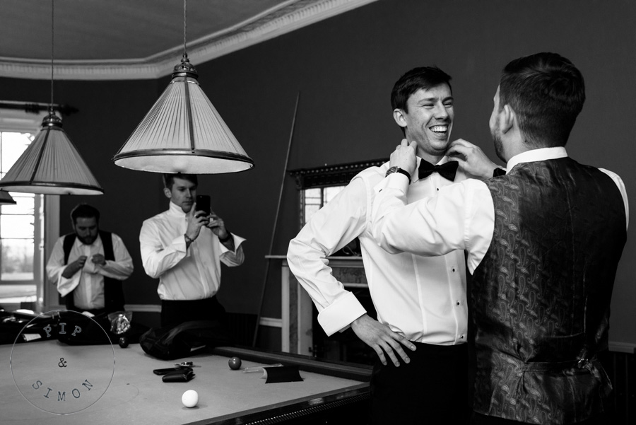 A groom laughs with friends as he gets ready for his wedding.