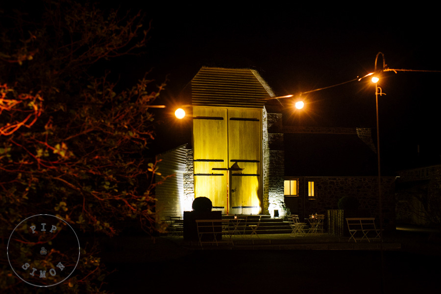 The Great Barn in Devon lit up at night.