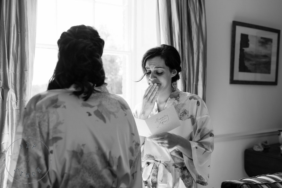 An emotional bride reading a card from her groom.