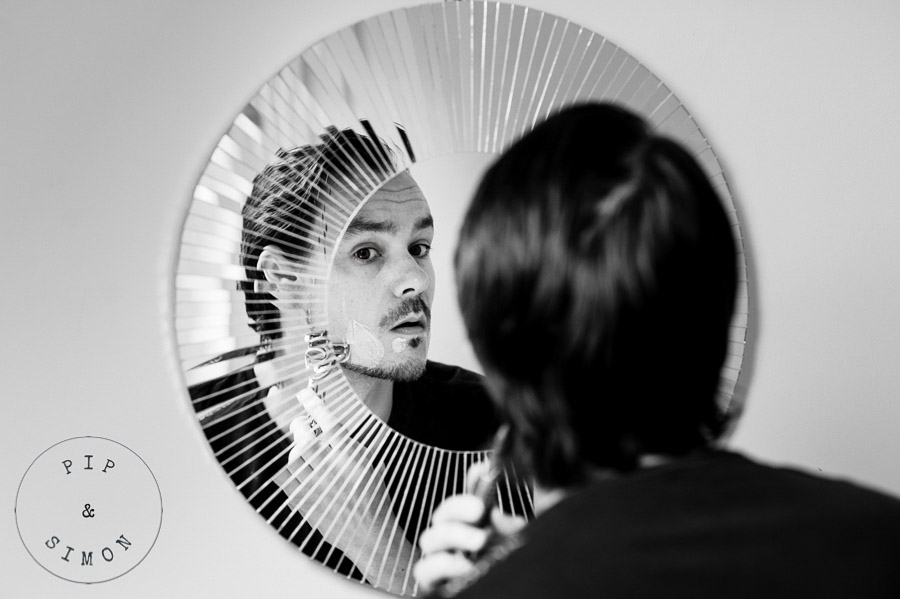 A groom shaves looking in a mirror on the morning of his wedding.