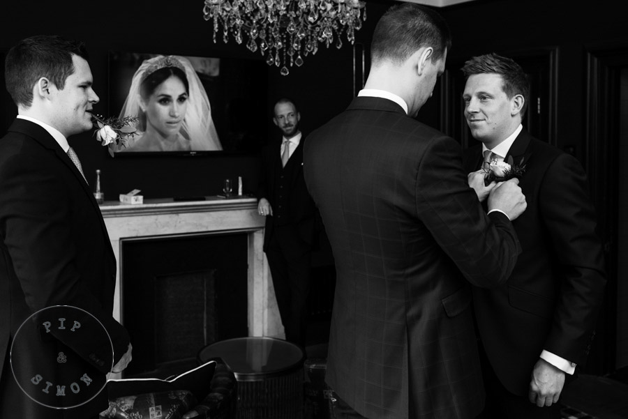 A groom gets ready while a royal wedding plays on a tv in the background.