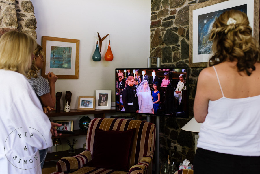 Bridesmaids watch a royal wedding on tv before they get dressed for a wedding.