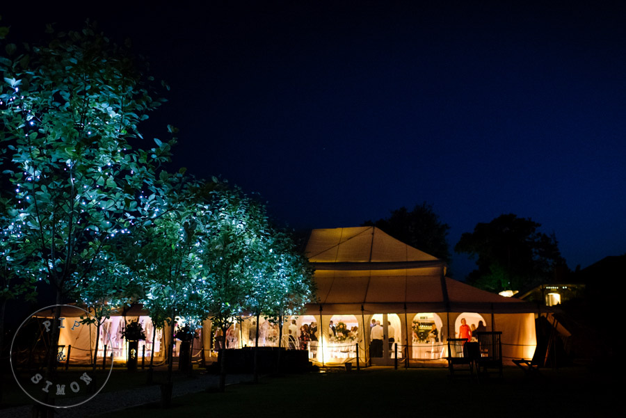 A marquee glows with the light of the party inside.