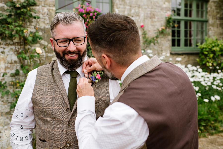 A groom and groomsman prepare on the morning of the wedding.