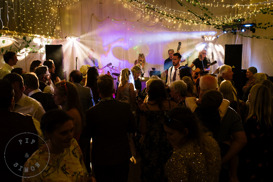 A band play to a crowd at a wedding reception party.