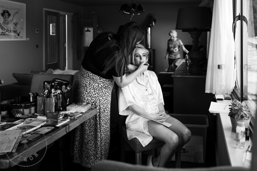 A bride and a make-up artist preparing for a wedding.